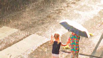 Kaksi tyttöä sateessa auringon paistaessa