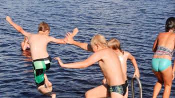 Poikia ja tyttöjä vesileikeissä laiturilla
