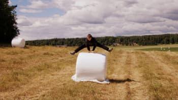Poika hyppää muoviin pakatun heinäpaalin yli