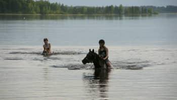Kaksi tyttöä ratsastaa hevosilla vedessä
