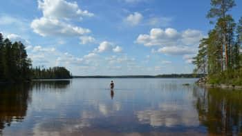 Kaukana ihminen kahlaa tyynessä vedessä kesäpäivänä
