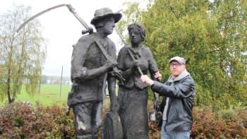 Mikko Maasola patsaan juurella.