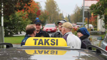 Miehiä ja naisia taksiauton kulmalla