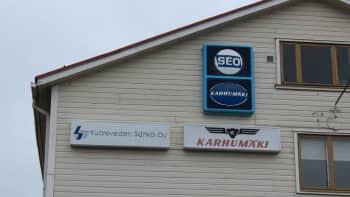 Kuoreveden Sähkön ja Karhumäen valomainokset puutalon seinässä Hallissa.