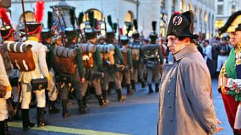 Napoleonia esittävä näyttelijä seuraa Saksin kuningaskunnan joukkoja esittävien näyttelijöiden ohimarssia Leipzigin taistelun 200-vuotisjuhlanäytöksen avajaisiltana.