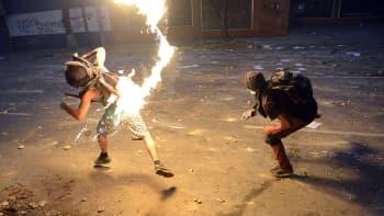 Venezuelalainen mielenosoittaja heittää polttopullon kohti mellakkapoliisia hallituksenvastaisen mielenosoituksen aikana.
