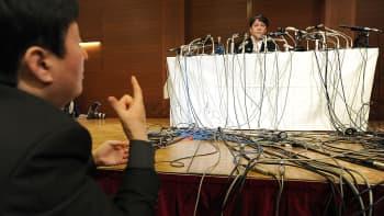 """""""Japanin Beethoveniksi"""" kutsuttu säveltäjä Mamoru Samuragochi seuraa viittomakielen tulkkia, joka kääntää hänelle toimittajien kysymyksiä lehdistötilaisuudessa."""