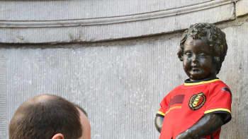 Mies pukee Belgian jalkapallomaajoukkueen uuden peliasun Manneken Pis -patsaalle Brysselissä.