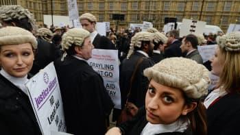 Brittiläiset asianajajat ympäri maan osoittavat mieltään hallituksen suunnittelemia oikeusapukustannusten leikkauksia vastaan parlamentin ulkopuolella Westminsterissa.