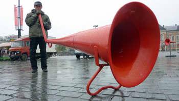Mies puhuu valtavaan megafoniin.