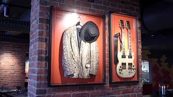 Kitara, takki ja hattu vitriinissä