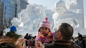 Vierailijoita Sapporon lumifestivaaleilla.