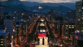 Iltanäkymä valaistuun kaupunkiin.