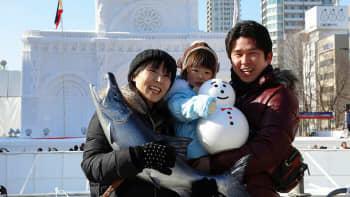 Vierailijoita Sapporon lumifestivaaleilla. Taustalla Manilan katedraalia esittävä lumiveistos.