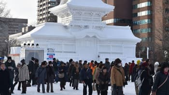 Vierailijoita Sapporon lumifestivaaleilla avajaispäivänä. Taustalla Kasugan temppeliä esittävä lumiveistos.