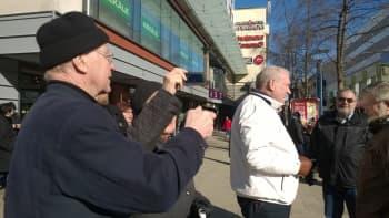Miehet katselee Jyväskylän keskustassa kännykkää.