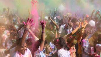 """Thaimaalaiset ja ulkomaalaiset heittävät värillistä jauhetta ilmaan, kun he osallistuvat """"Miles for Smiles 2015"""" hyväntekeväisyysjuoksuun"""