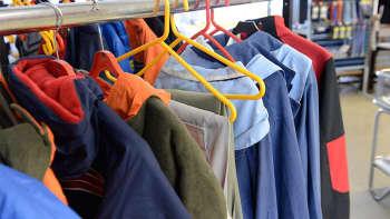 Kuvassa vaaterekki. Vaatteita hangareissa.