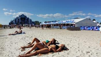 Nuoret naiset lekottelevat auringonpaisteessa rannalla.