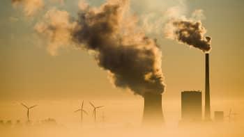 Tuulivoimaloita ja savuava jäähytystorni sekä savupiippu nousevat sumusta.