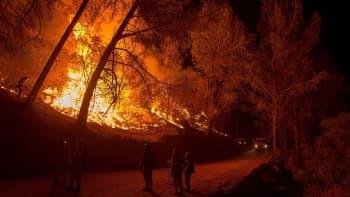 Palomiehet seuraavat yläpuolellaan rinteessä raivoavaa maastopaloa.