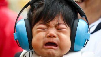 Vauva itkee kuulosuojaimet päässä.