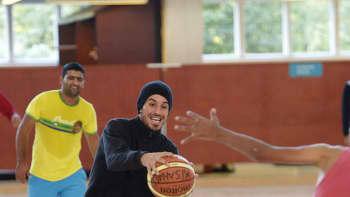 Turvapaikanhakijoita pelaamassa koripalloa.