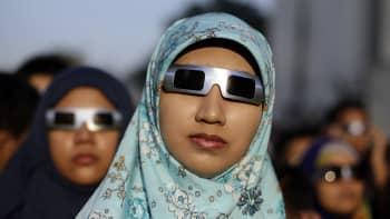 Ihmisiä katsomassa pimennyslaseilla auringonpimennystä Jakartassa Indonesiassa.