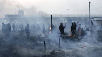 Pakolaisia savuavilla raunioilla.