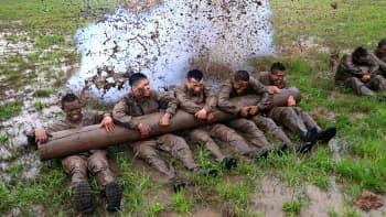 Viisi sotilasta makaa mutavellissä ja pitelee tukkia sylissään.