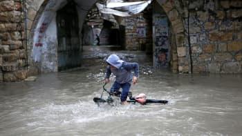 Poika kaatuneen pyörän kanssa tulvivalla kadulla.