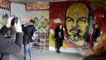 Turistit valokuvaavat seinämaalauksia Skrundan entisessä kulttuurikeskuksessa Latviassa