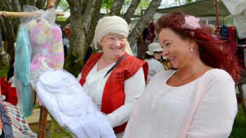 Käsitehtyä pukua lapsenlapselle katsoo Eevaliisa Lahdenkauppi. Myyjä Kaija Leinonen. Peräpohjolan markkinat