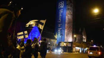 Ihmisiä liikkeellä Suomen lippujen kanssa Helsingin keskustassa kansallismuseon edustalla.