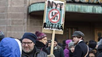 Mies pitelee kylttiä joka vastustaa natsismia.