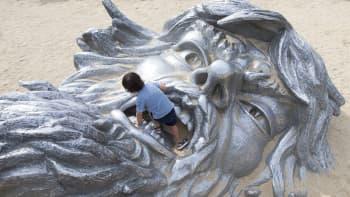 """Lapsi leikki kaksikymmentäkaksimetrisen """"Awakening"""" -patsaan suussa Marylandissa, Yhdysvalloissa 10. elokuuta."""