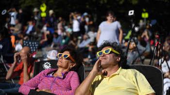 Ihmiset katselevat auringonpimennystä.