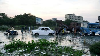 Kyläläiset tarpovat ajoneuvojen keskellä veden alle jäämää tietä pitkin Maldassa 21. elokuuta.