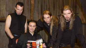 Apocalyptica -bändin pojat Paavo Lötjönen (vas.), Eicca Toppinen ja Perttu Kivilaakso sekä H.I.M:n Ville Valo (etualalla kirjan kanssa), Apocalyptican Bittersweet -biisin videon kuvauksissa Angel studioilla Herttoniemessä.