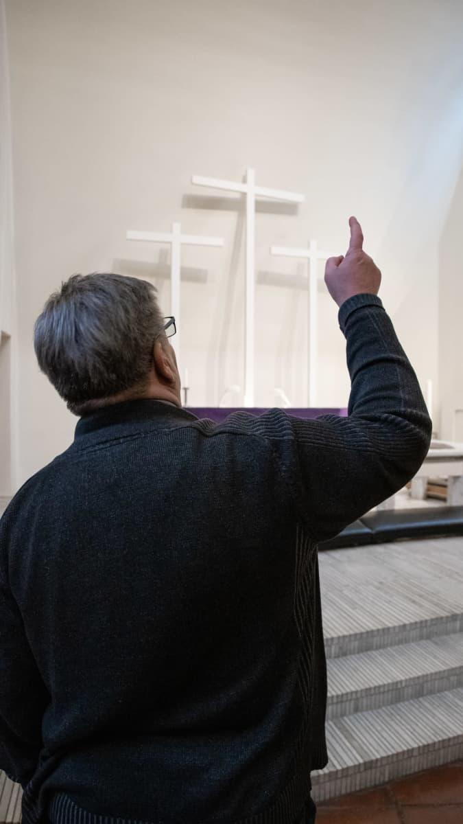 Kiinteistöpäällikkö Jari Nousiainen osoittaa Kolmen ristin kirkon alttaria, johon aamuauringon säteet osuvat.