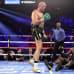 Tyson Fury seisoo kehässä, Deontay Wilder istuu.