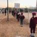 lapset jonottavat turvavälein koulun pihalla Windhoekissa, Namibiassa