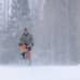Mies pyöräilee lumisateessa.