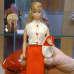 Henkilö pitelee vanhaa Barbie-nukkea.