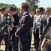 Nuorukaiset kuuntelevat hautajaisissa ruusut käsissään
