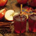 Joulupöydässä kanelitankoja, glögiä ja omenoita.