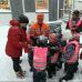 Kuvassa vasemmalla olevat Pirre Mahlberg ja Jani Kemppe jakavat Sinetän päiväkodin lapsille heijastimia päiväkodin pihalla.
