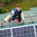 Jouni Koskela esittelee katolla aurinkopaneeleitaan.