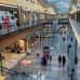 Yleisnäkymää Isosta Omenasta, ihmisiä kävelee muotiliikkeiden ohi kahdessa kerroksessa, rullaportaat.