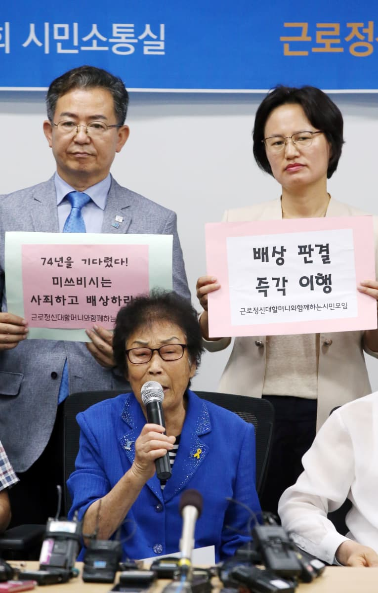 Yang Geum-deok mikrofoni kädessä, taustalla kaksi ihmistä.